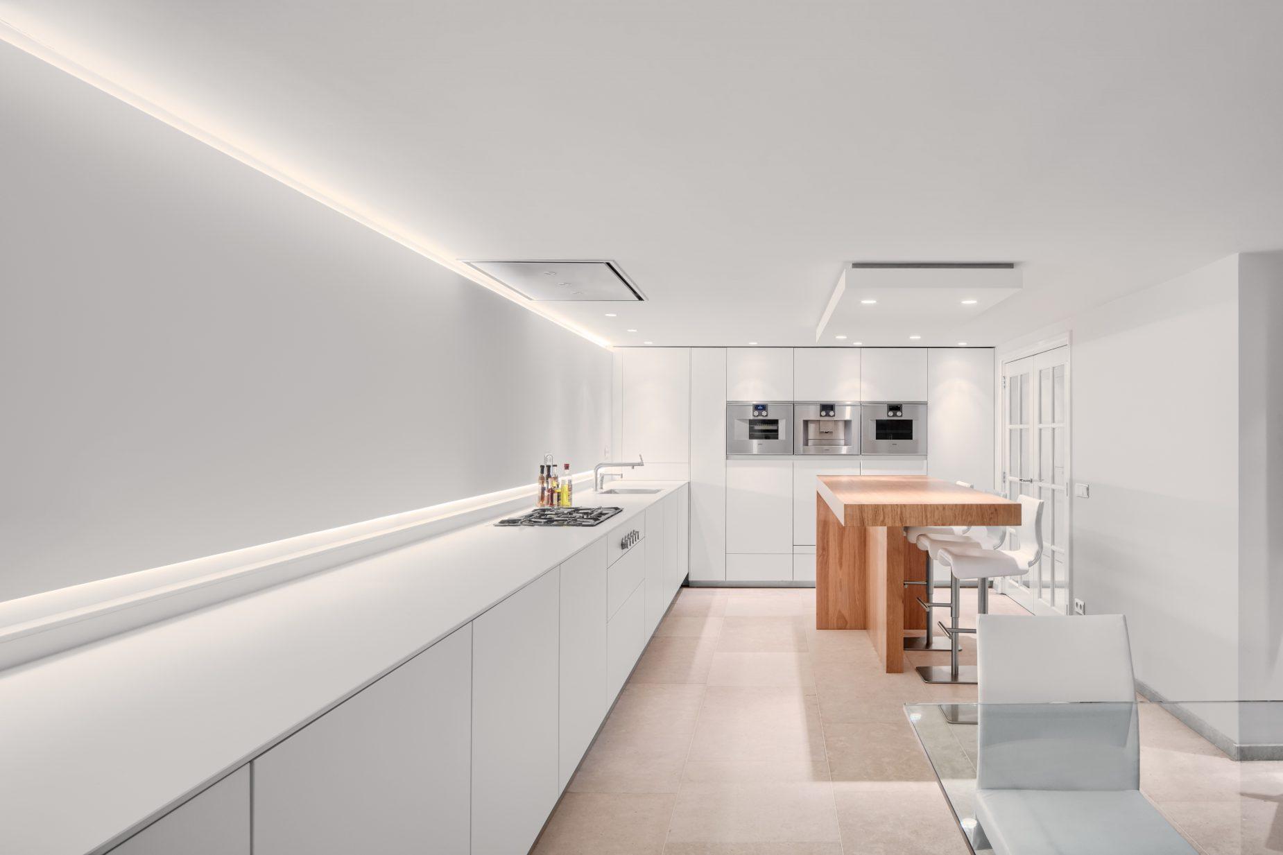 Moderne witte keuken met hout en verlichting ontwerp door binnenhuis architect Maxim Winkelaar.