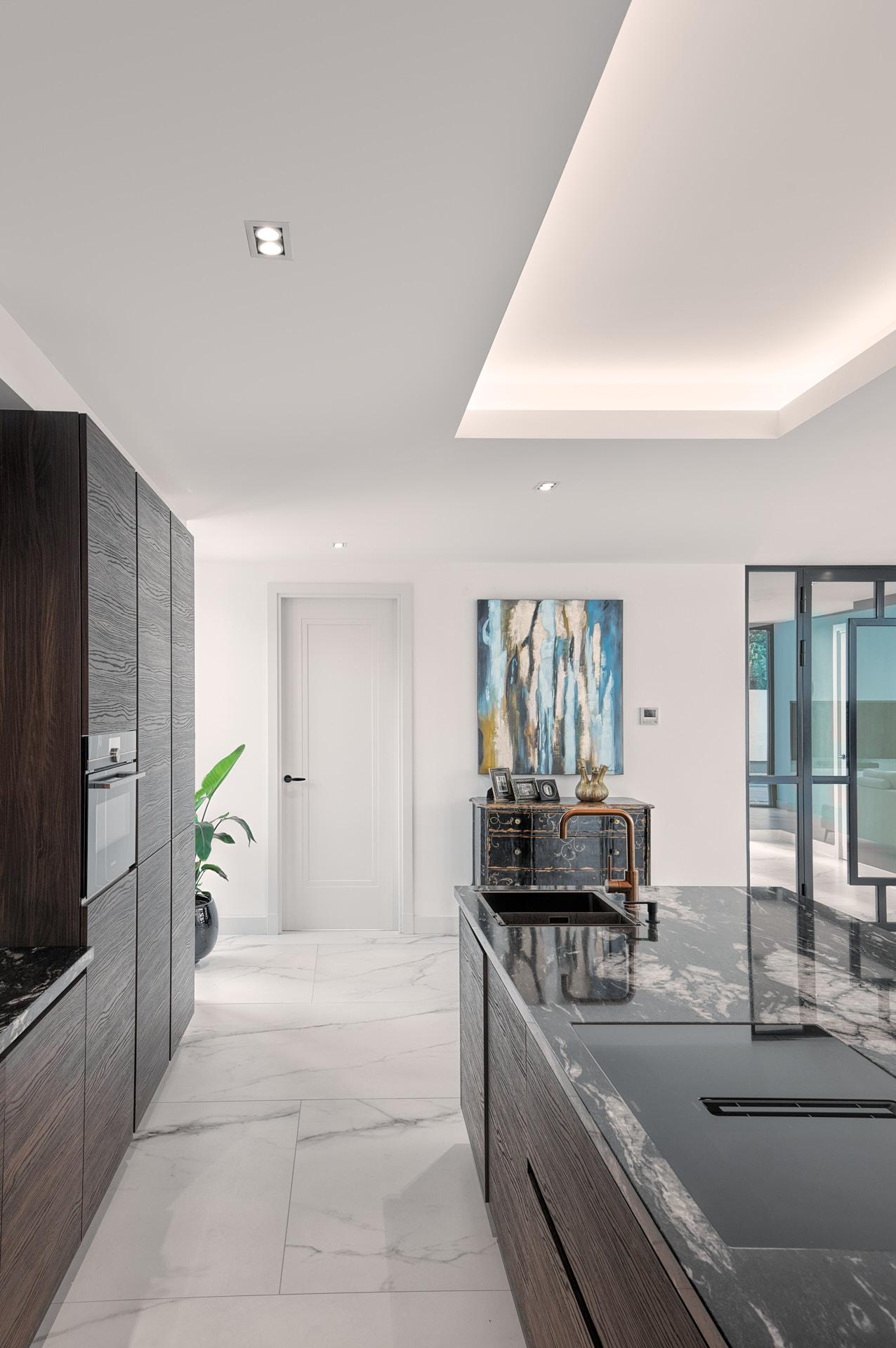 Keukenontwerp met marmeren tegels en plafondverlichting.