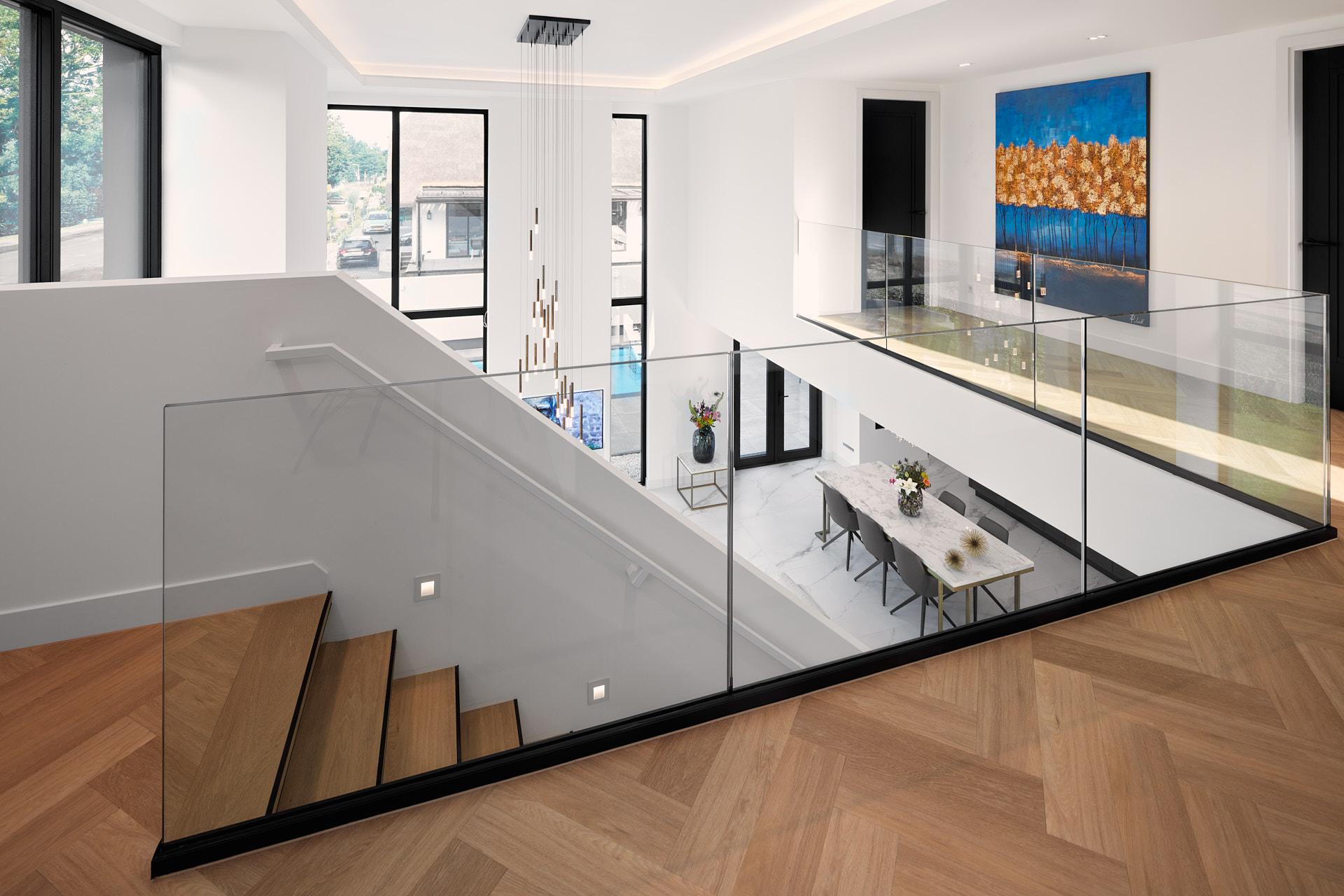 Houten visgraatvloer met vide en kroonluchter bij woonkamer door interieurarchitect Maxim Winkelaar.