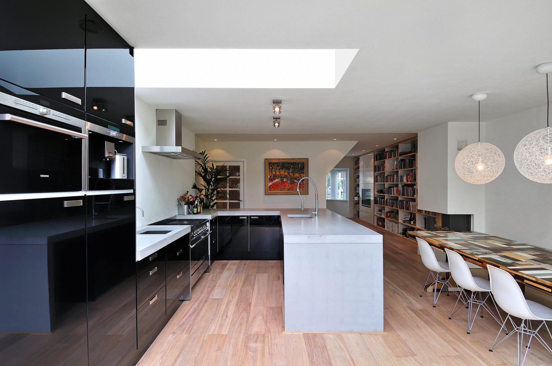 Renovatie van jaren 30 woning in Amstelveen door Amsterdamse architect Maxim Winkelaar. Zwarte keuken en beton aanrechtblad.