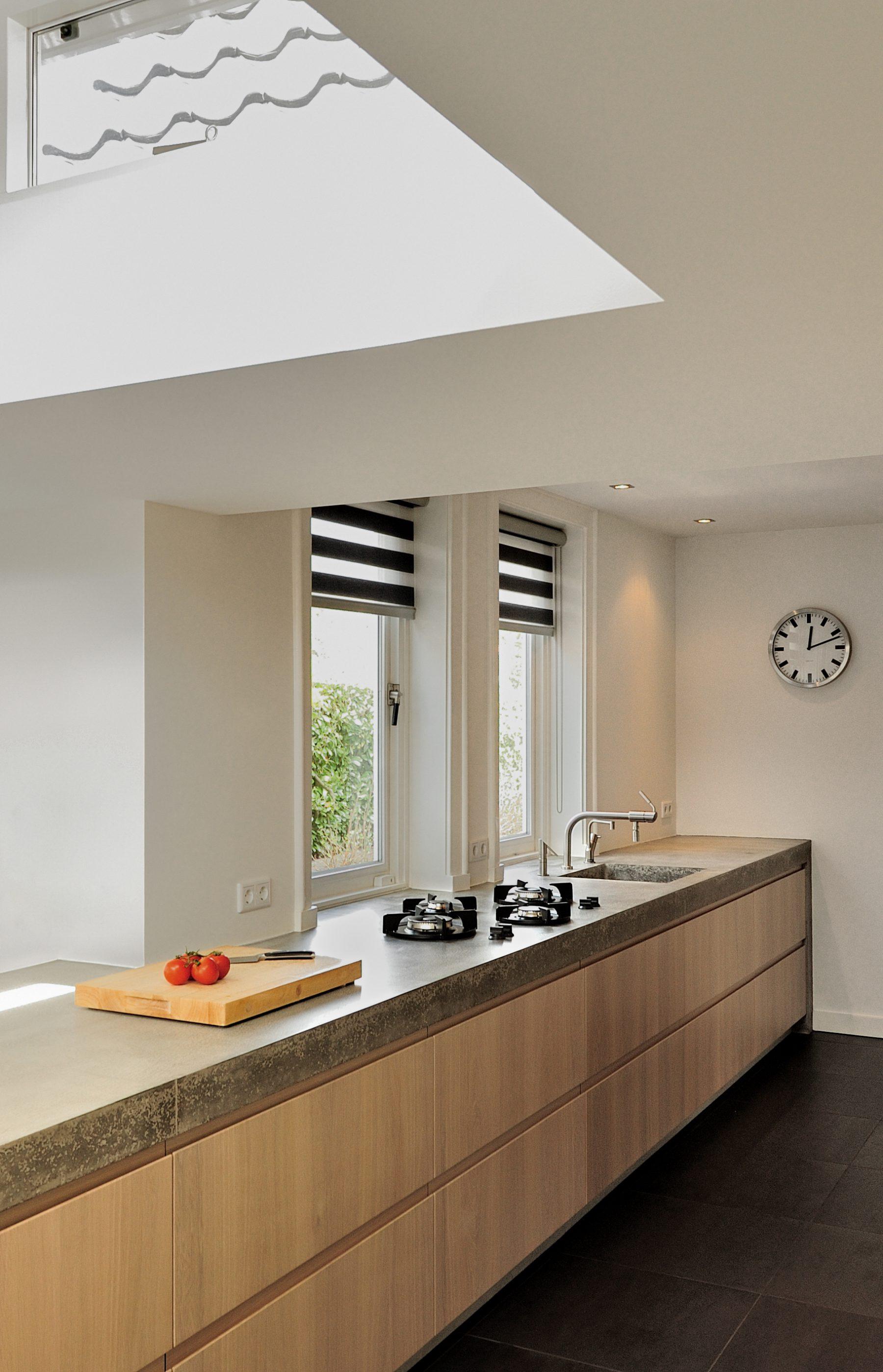 Wij hebben een nieuw ontwerp gemaakt voor de keuken en bijkeuken met een uitbouw. Om de huidige keukenruimte te betrekken bij de uitbouw hebben wij het aanrecht als verbindende element gemaakt. Het bijna 8 meter lange aanrechtblad is gemaakt van beton en is op locatie (in het werk) gestort en gepolijst. Het betonnen aanrecht bevat geïntegreerd 'pitt cooking'. De kasten van de keuken zijn gemaakt van licht eiken. Het aanrechtblad loopt over naar een bargedeelte. Bij het bargedeelte zit in het betonnen aanrecht plaatselijk een elektrische 'vloerverwarming', op deze manier is de 'kou eraf' als men aan de bar zit. Boven het bargedeelte is het dak plaatselijk verhoogd met daarin ramen rondom. Door deze ramen komt een mooie natuurlijke lichtinval in het eetgedeelte.