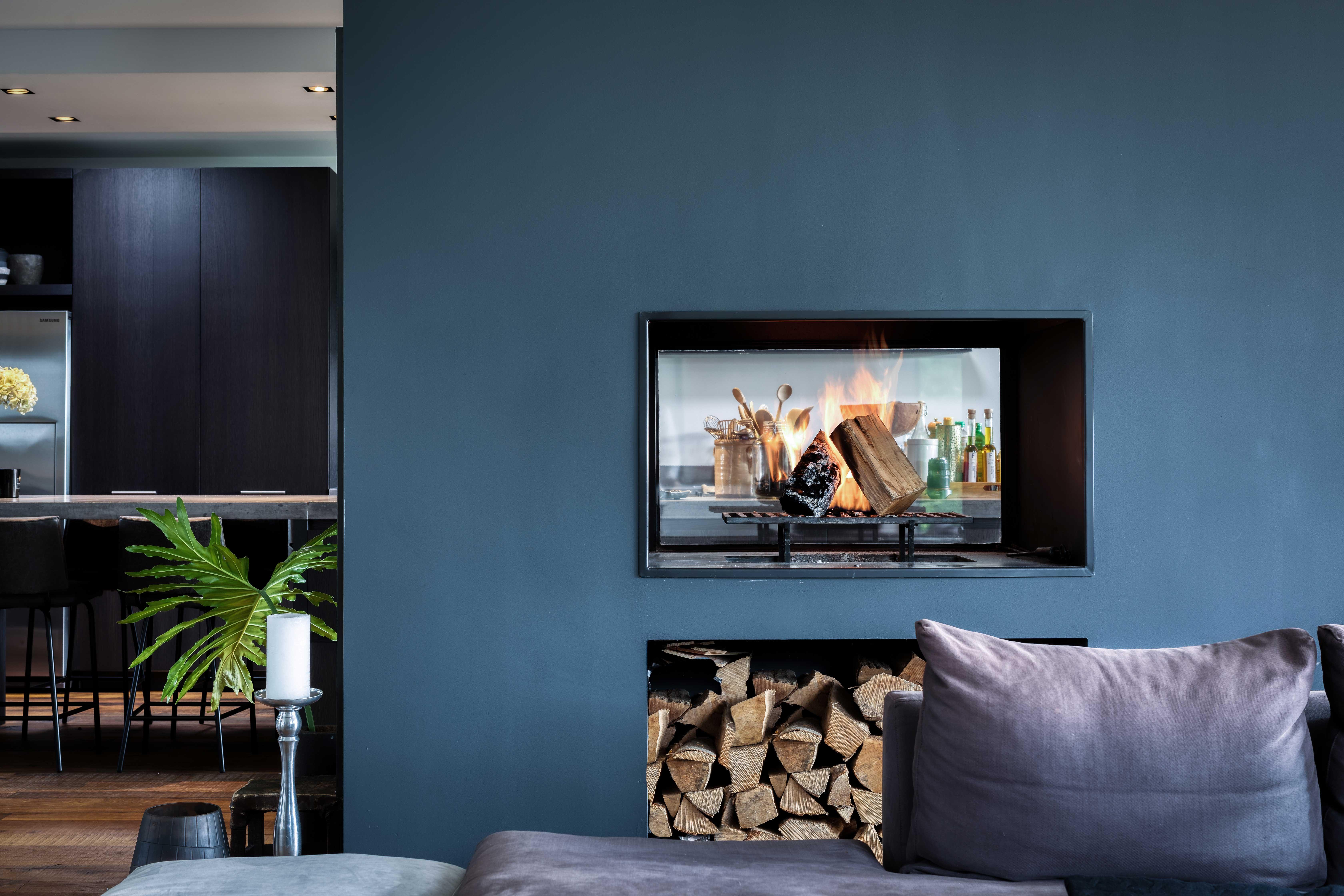 Maxim Winkelaar Architecten uit Amsterdam heeft een moderne nieuwbouwvilla aan het water van de Vinkeveense Plassen ontworpen en gebouwd. Prachtige doorkijk haard tussen keuken en woonkamer.